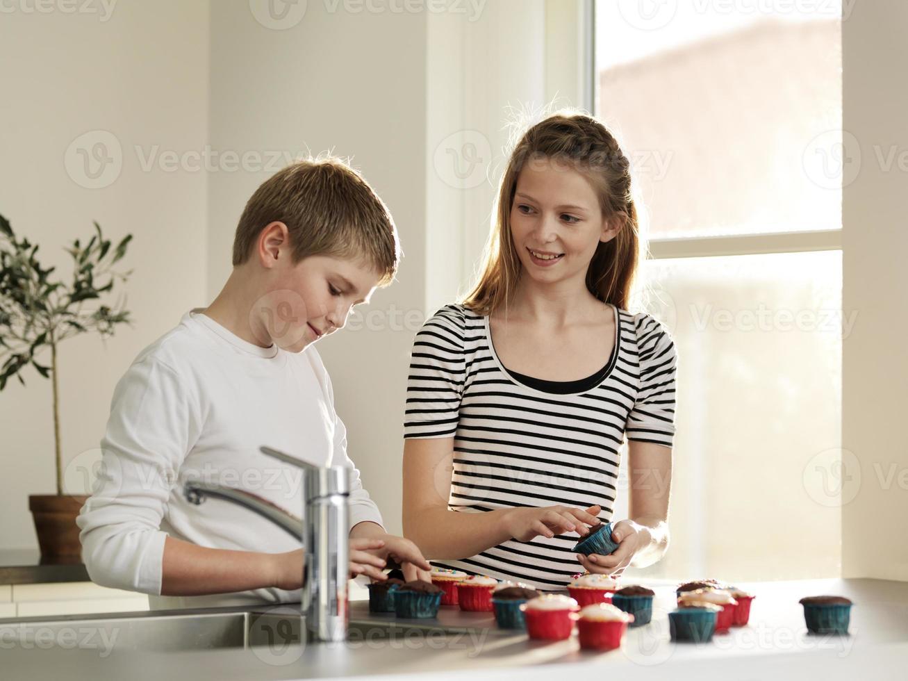 Kinder, die zusammen Cupcakes dekorieren foto