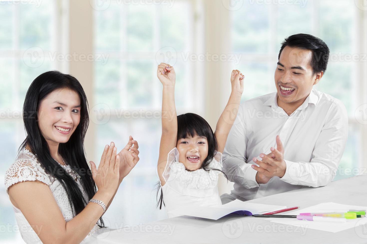freudige Familie, die gemeinsam die Schularbeiten beendet foto