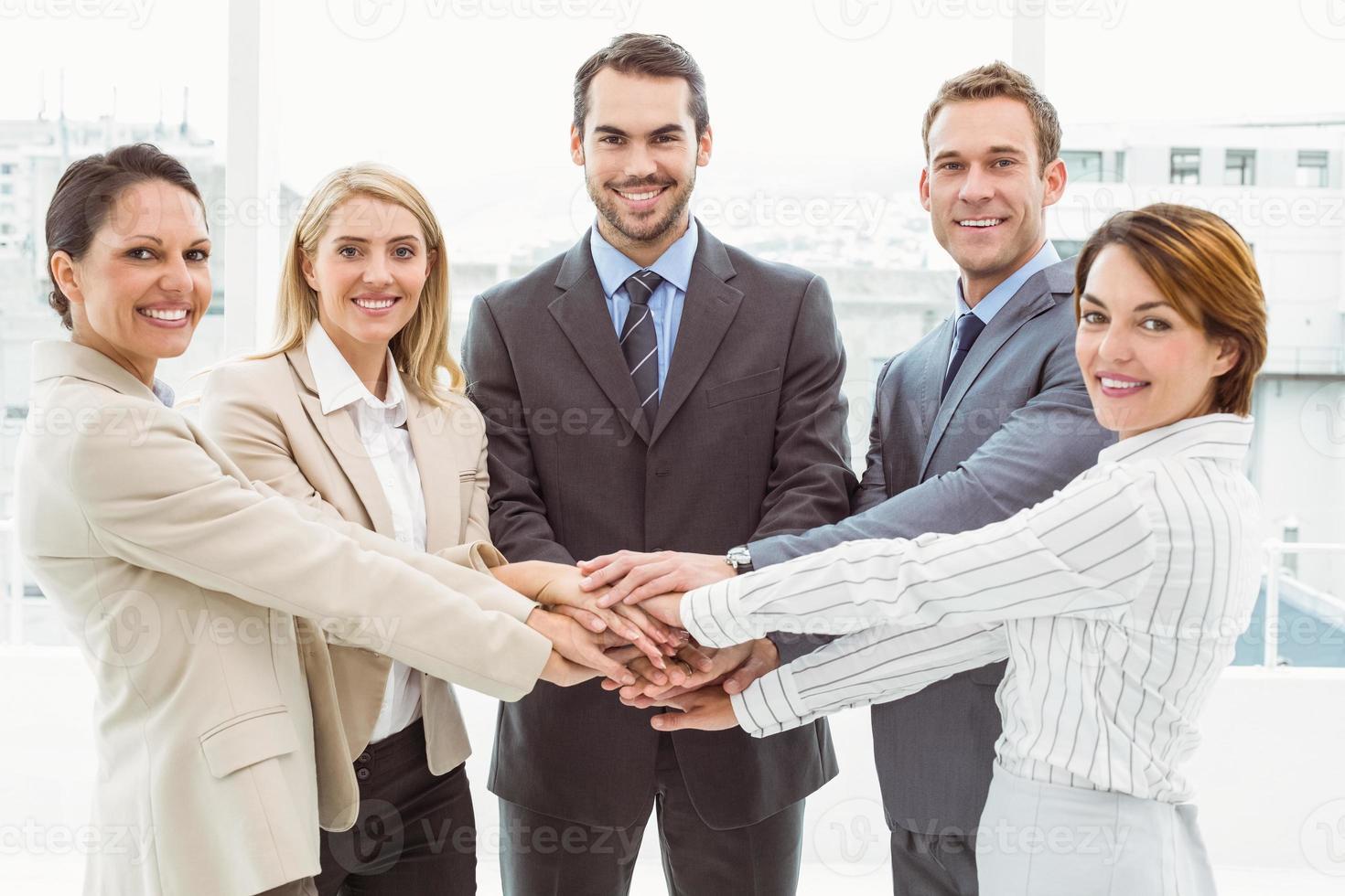 glückliche Führungskräfte, die im Amt Hände zusammenhalten foto