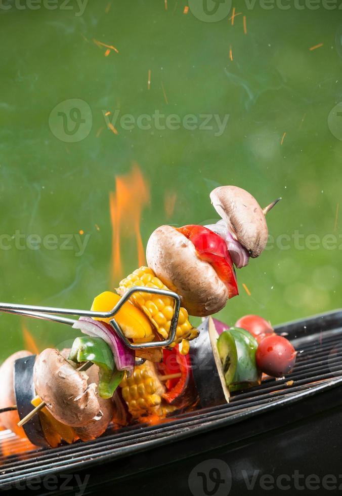 Gegrillte vegetarische Spieße in Flammen foto