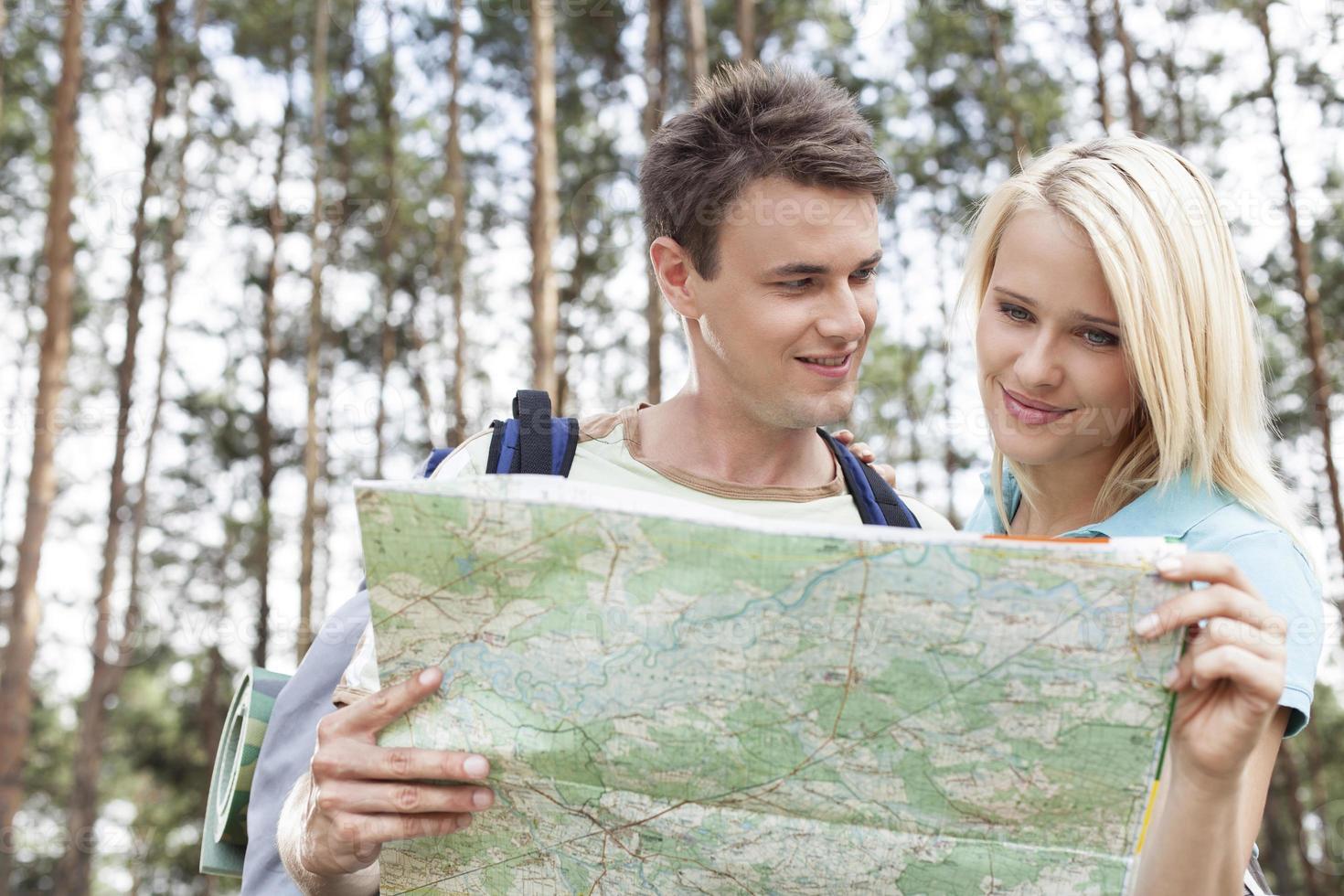 glückliche junge Rucksacktouristen, die Karte im Wald lesen foto
