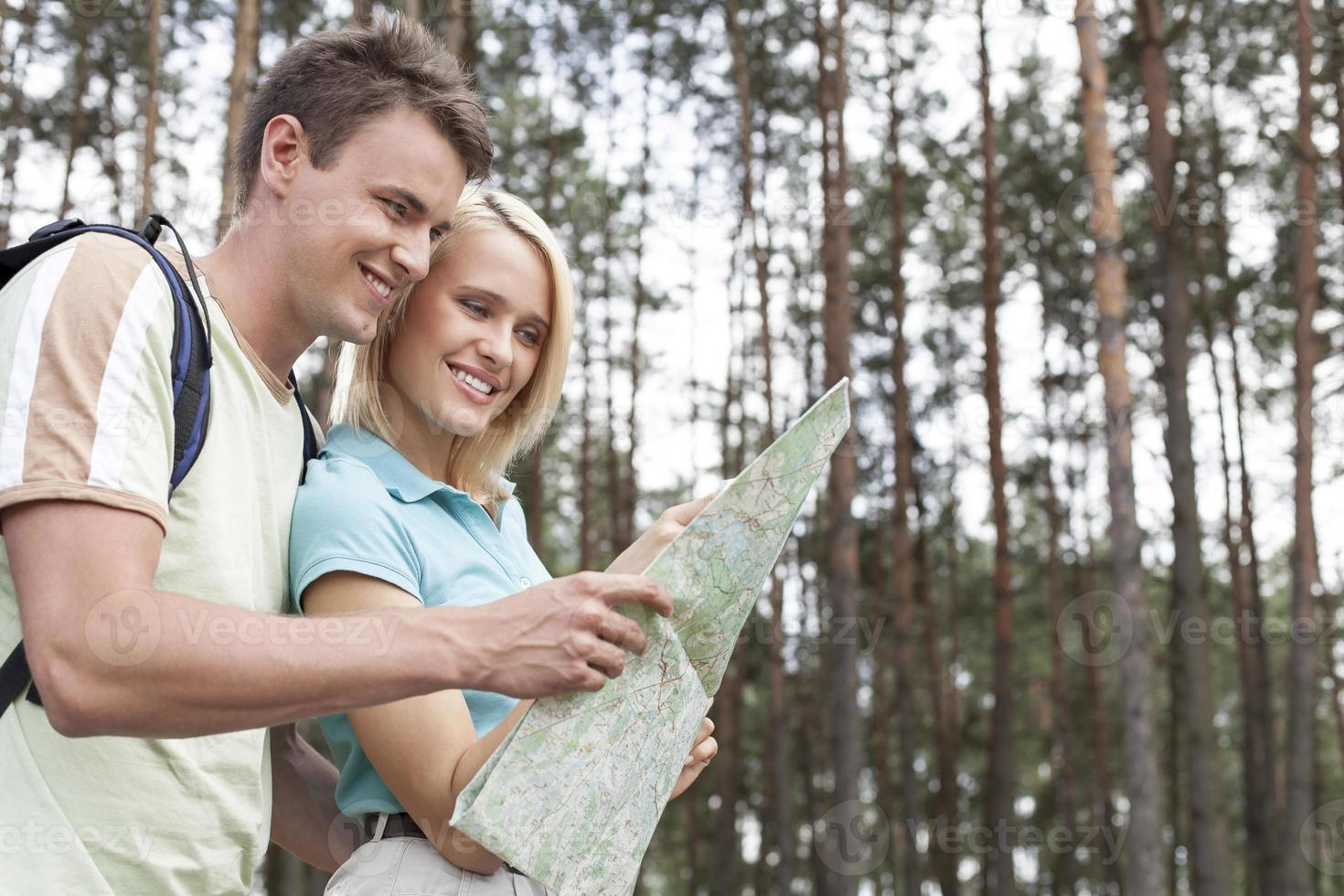 glückliche junge Rucksacktouristen, die Karte im Wald betrachten foto