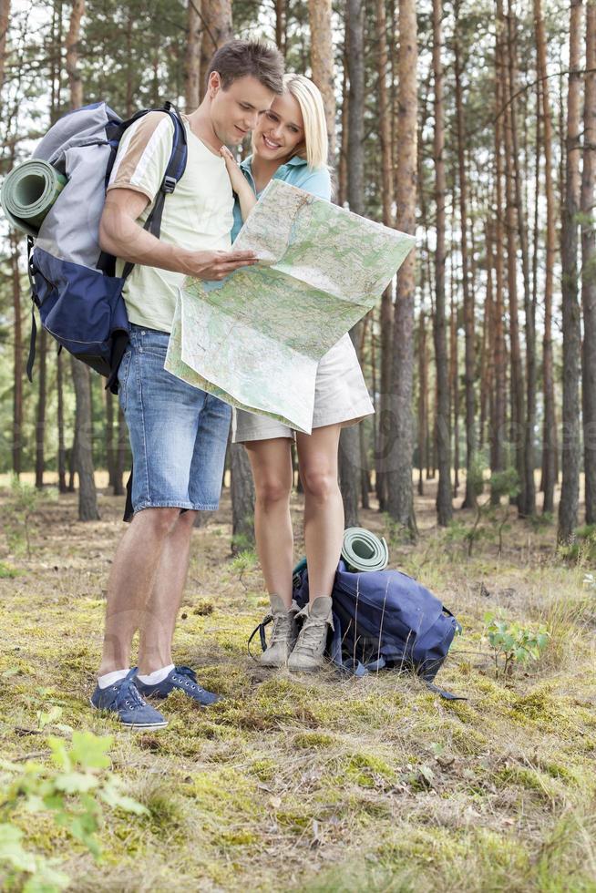 in voller Länge des jungen Wanderpaares, das Karte im Wald liest foto