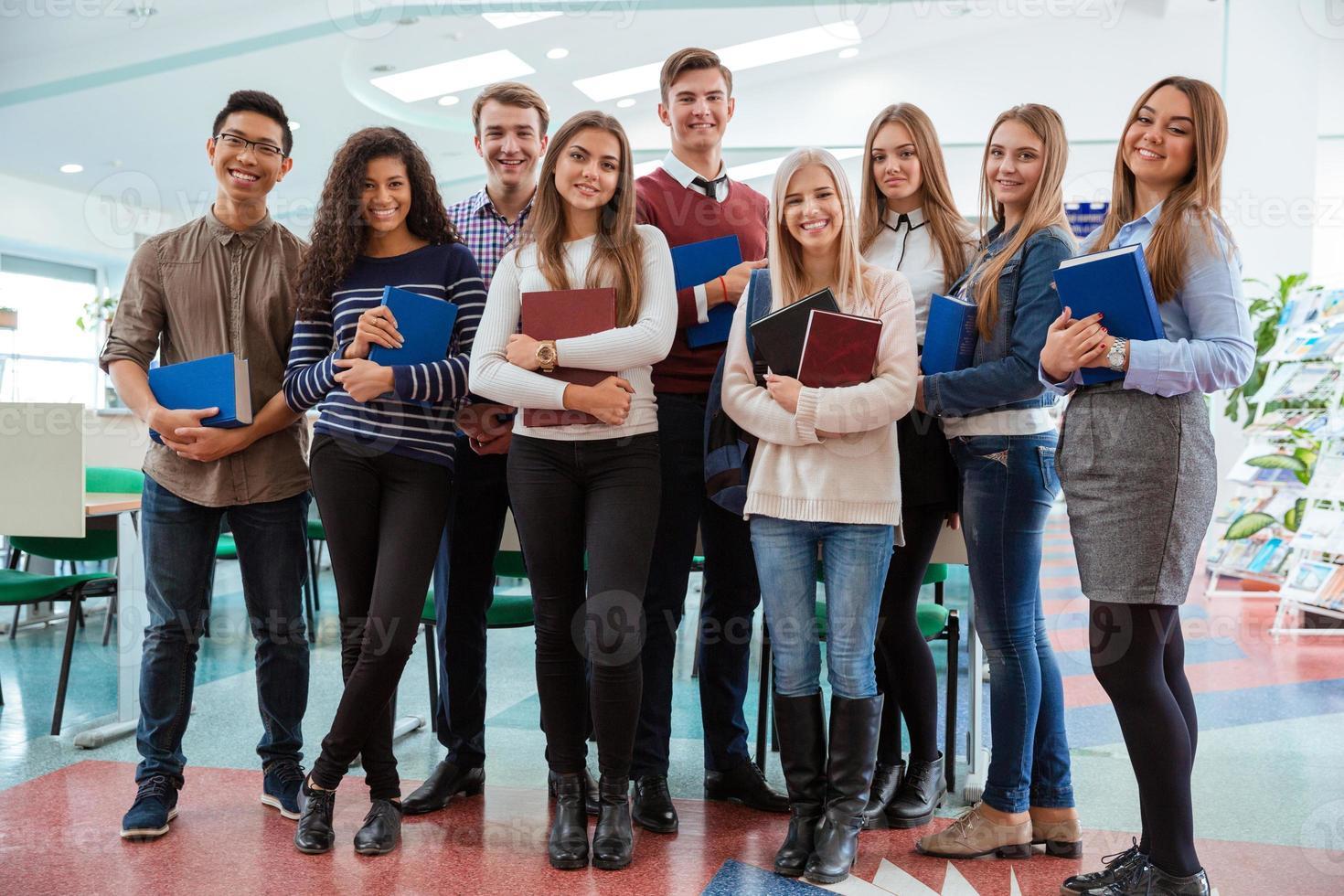 glückliche Schüler, die zusammen im Klassenzimmer stehen foto