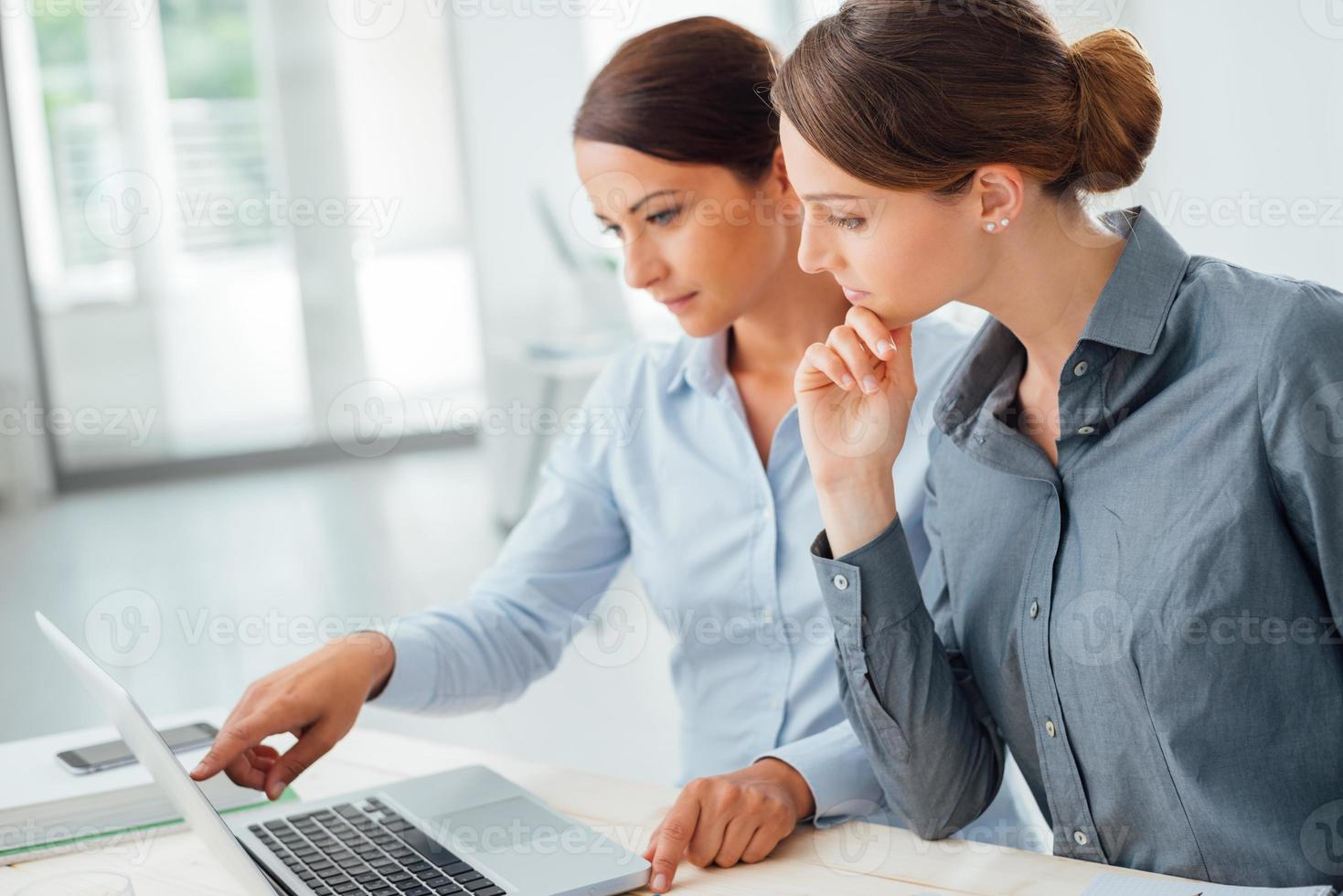 Geschäftsfrauen, die zusammen an einem Laptop arbeiten foto