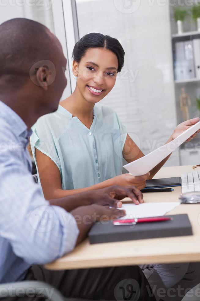 glückliches Geschäftsteam, das am Schreibtisch zusammen arbeitet foto