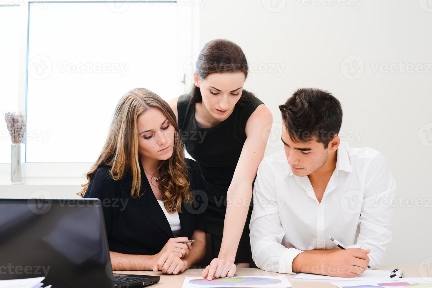 Geschäftsteam für junge Leute, die im Besprechungsraum zusammenarbeiten foto