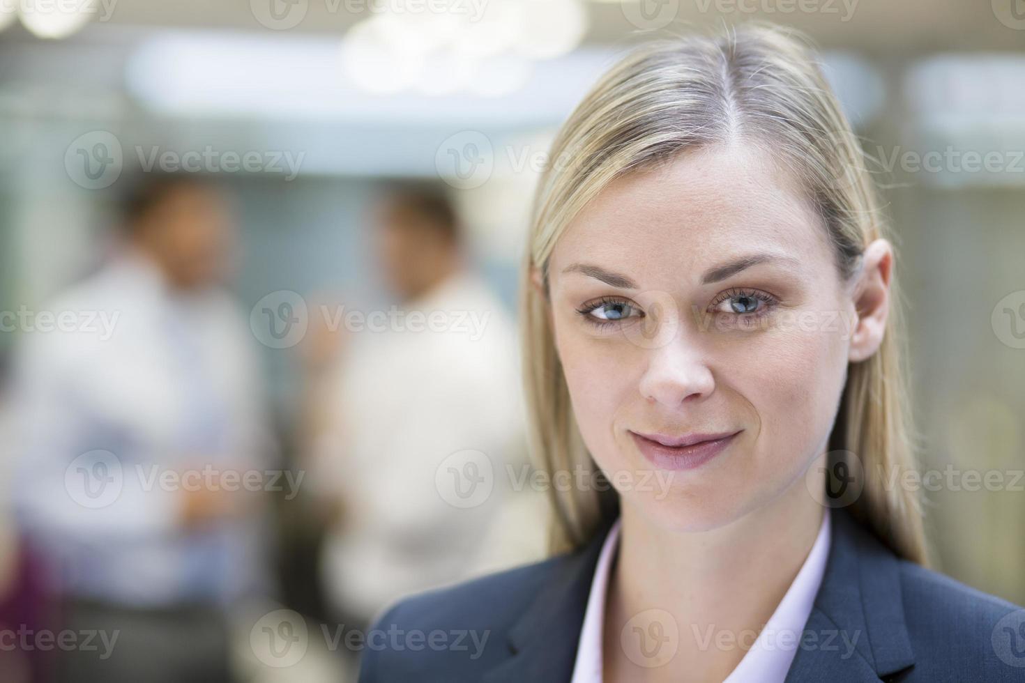 hübsche Geschäftsfrau, die aufwirft, während Kollegen zusammen im Hintergrund sprechen foto