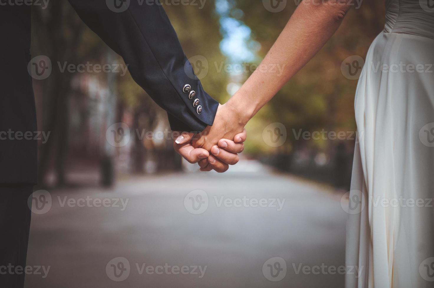 Paar Hand im Park zusammenhalten foto