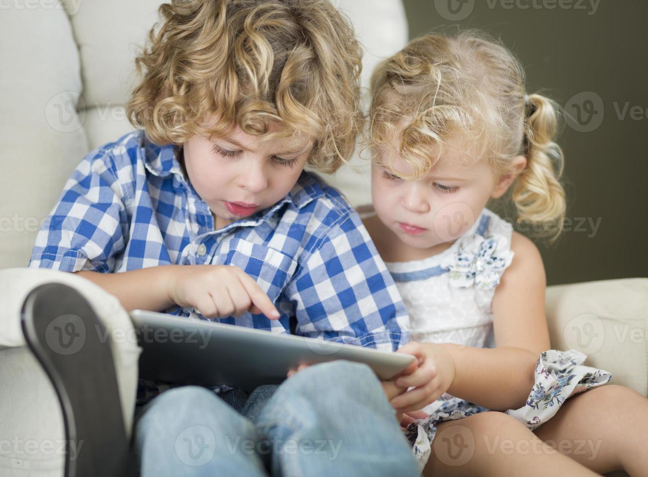 junger Bruder und Schwester, die zusammen ihr Computer-Tablet benutzen foto