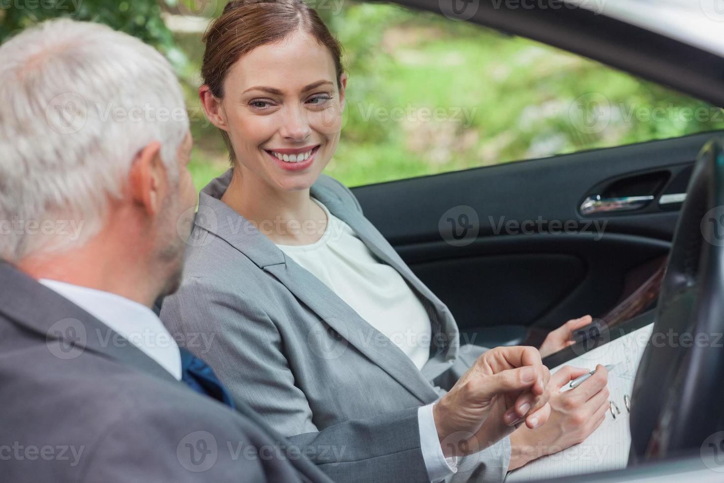 lächelnde Partner, die im noblen Auto zusammenarbeiten foto