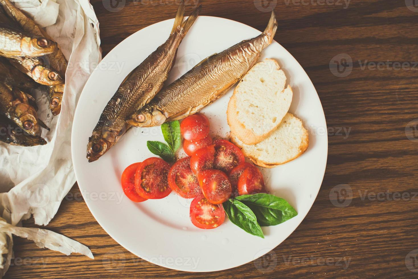 geräucherter Fisch auf Papier, Holztisch, Pfeffermühle foto