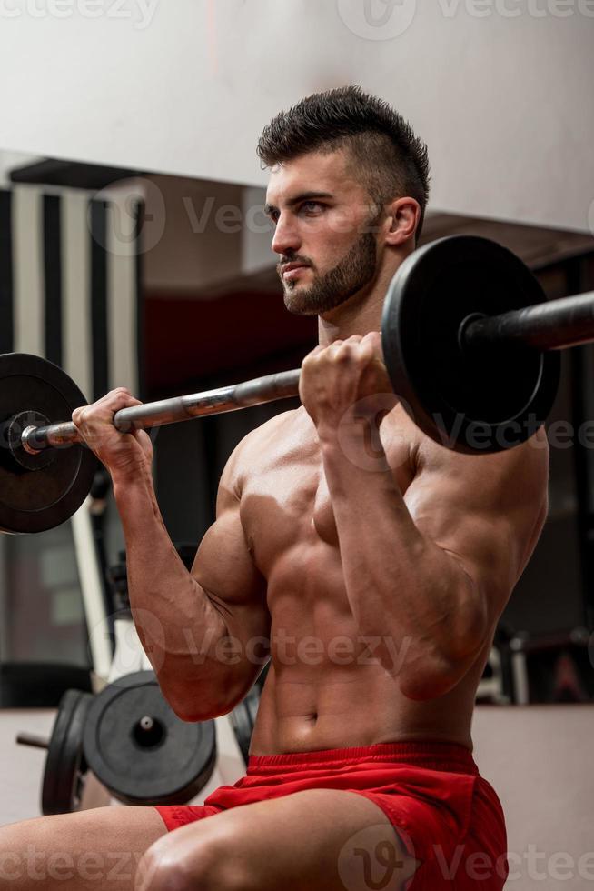 muskulöse Männer, die schweres Gewicht für Bizeps trainieren foto