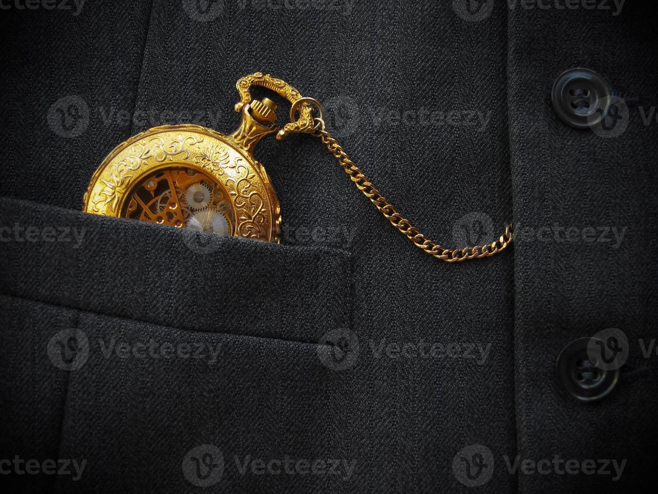 goldene Taschenuhr mit schwarzer Herrenweste foto