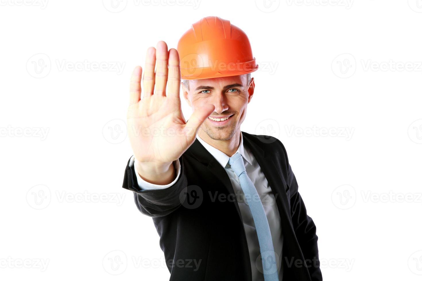 Geschäftsmann im Helm zeigt Stoppgeste foto