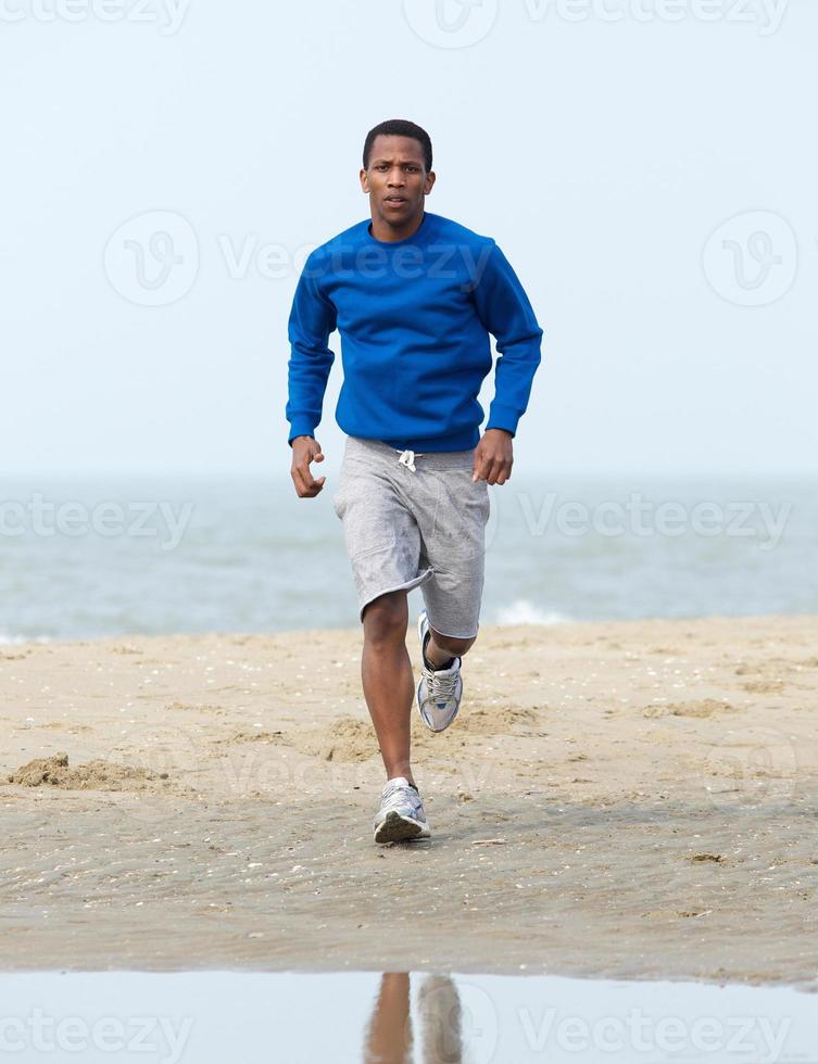 Afroamerikanermann, der am Strand joggt foto