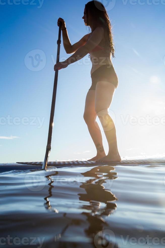 weibliches Paddleboarding bei Sonnenaufgang foto