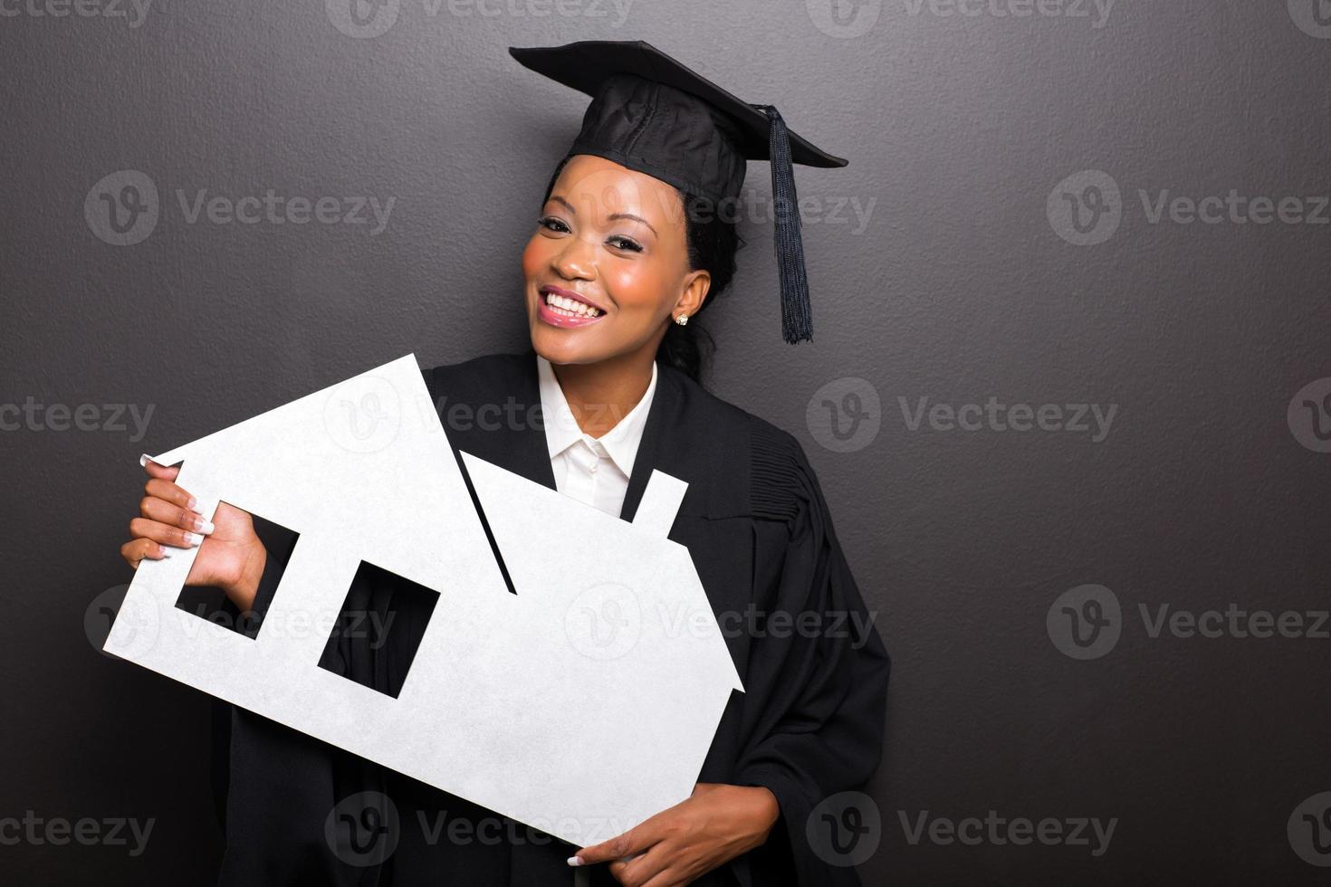 afrikanischer weiblicher Universitätsabsolvent, der Papierhaus hält foto