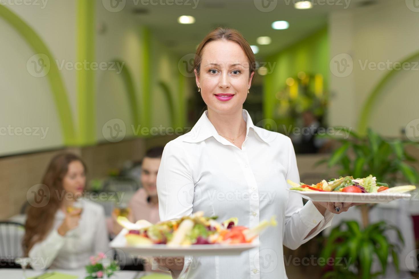 Kellnerin serviert Gästetisch foto