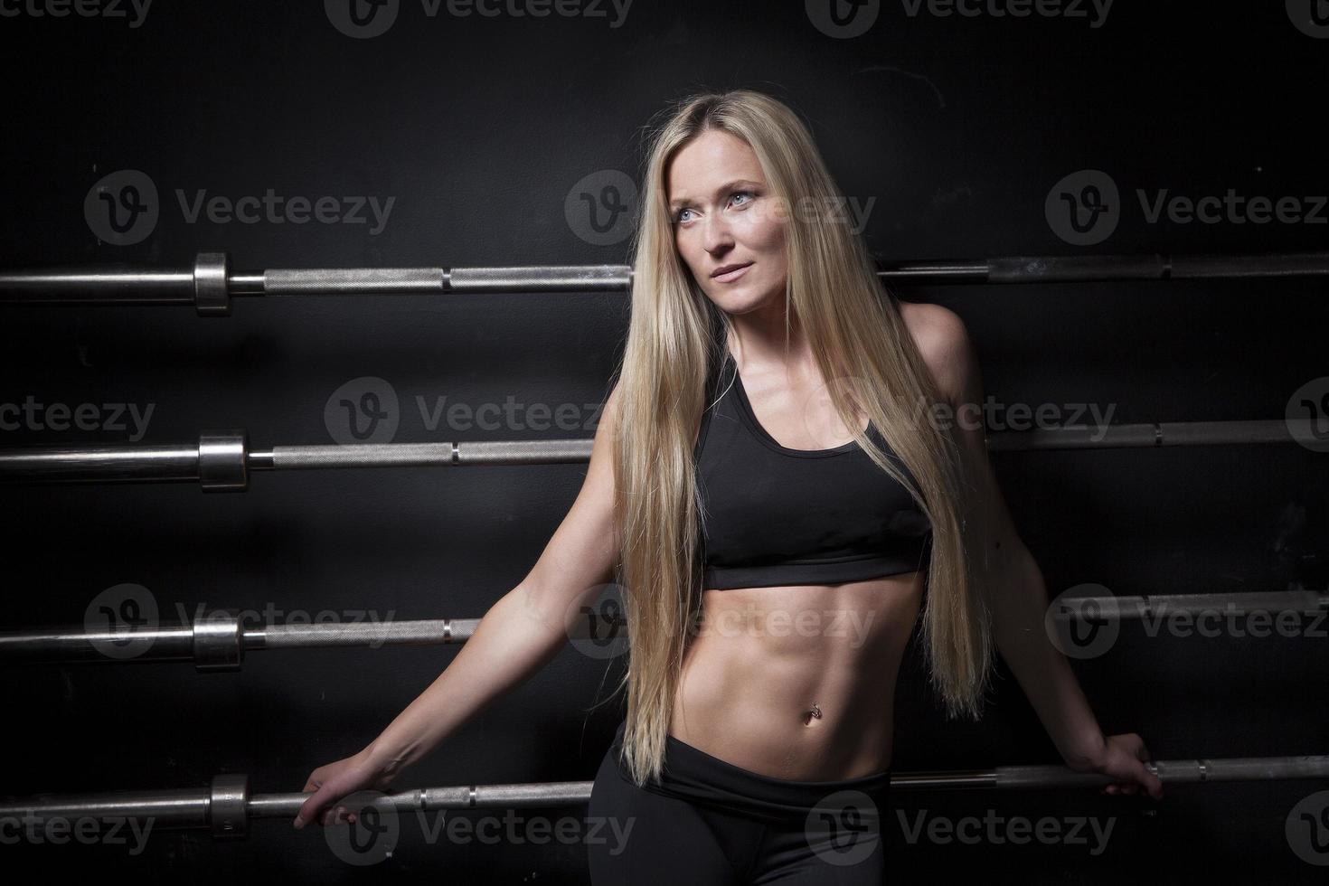 Sportlerin posiert mit Langhantel foto