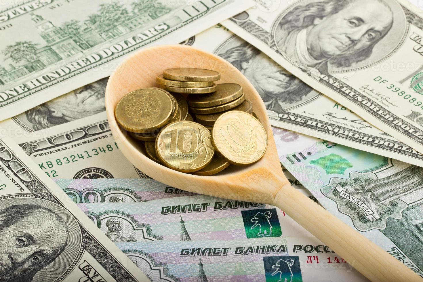 Löffel mit Münzen auf einem Hintergrund des Geldes foto