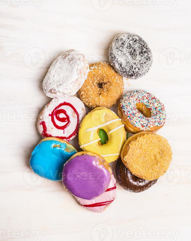 Haufen bunter Donuts auf weißem hölzernem Hintergrund, Draufsicht foto