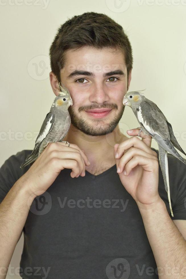 junger Mann hält zwei Papageien auf jeder Hand foto