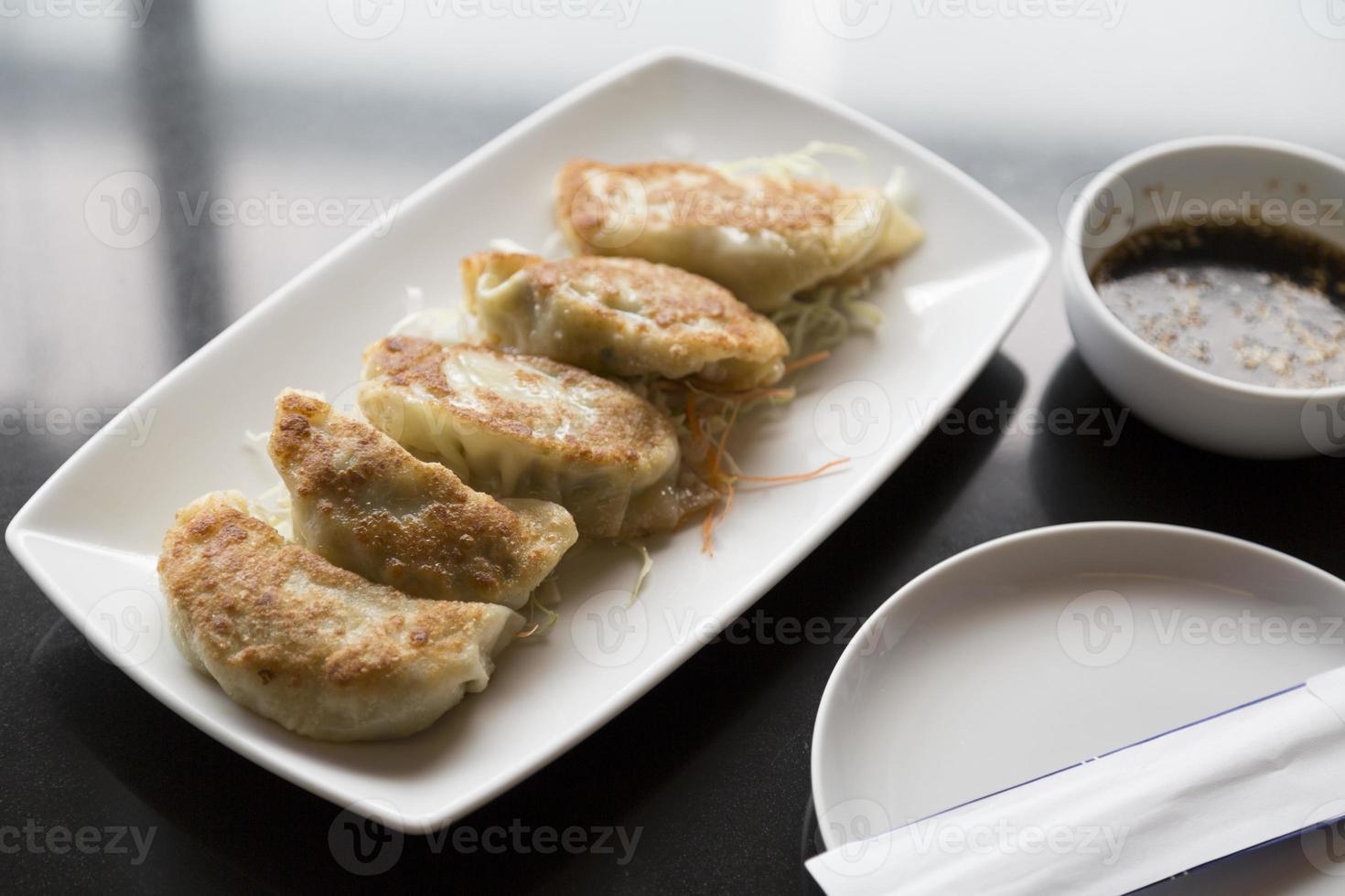 Jiaozi, chinesischer Knödel auf schwarzem Tisch mit Sauce foto