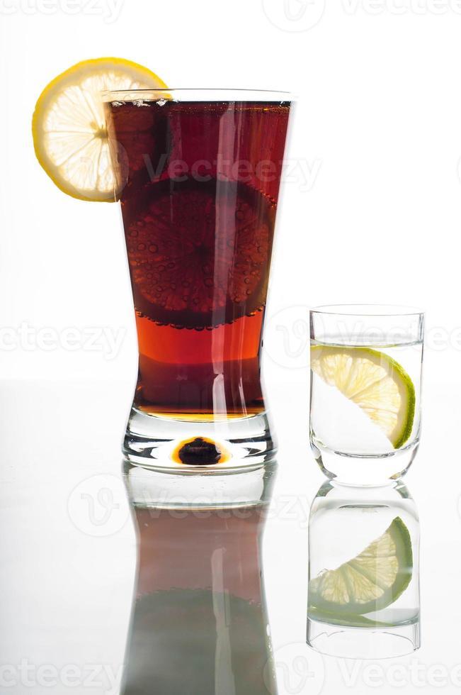 Glas Cola mit Zitronenscheiben und Wodka foto