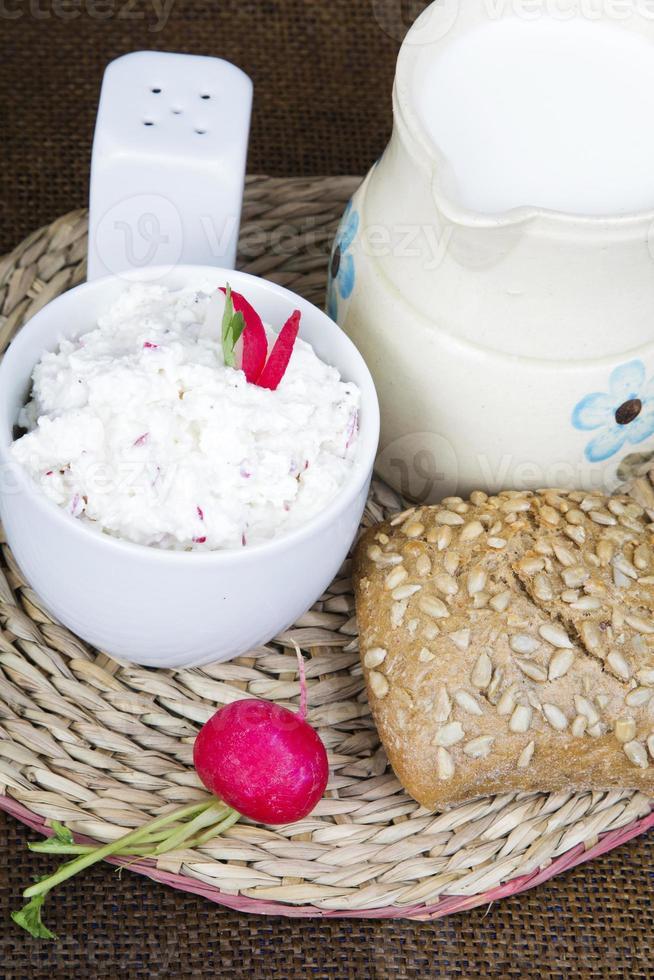 Hüttenkäse mit Radieschen, Milchkännchen und Vollkornbrötchen foto