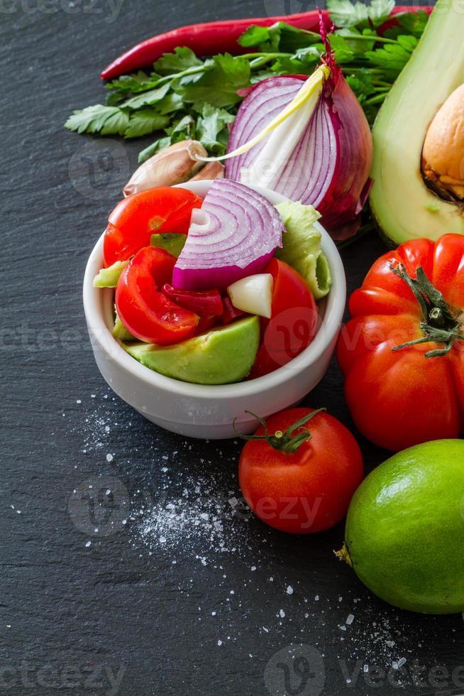 Guacamole Zutaten - Avocado, Tomaten, Zwiebeln, Knoblauch, Limette, Petersilie foto