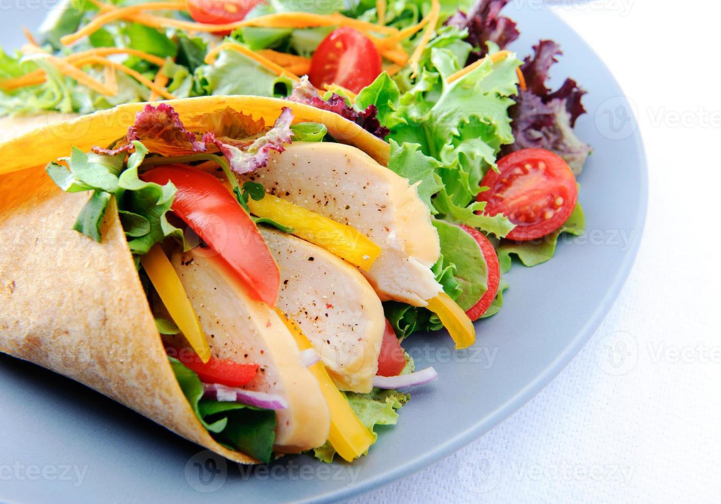 Nahaufnahme auf frischem Hühnchengemüse Wrap mit Beilagensalat foto