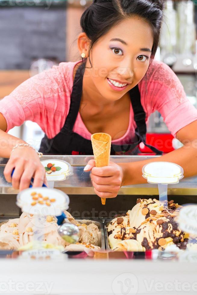 lächelnde Arbeiterin in der Eisdiele, die einen Kegel hält foto