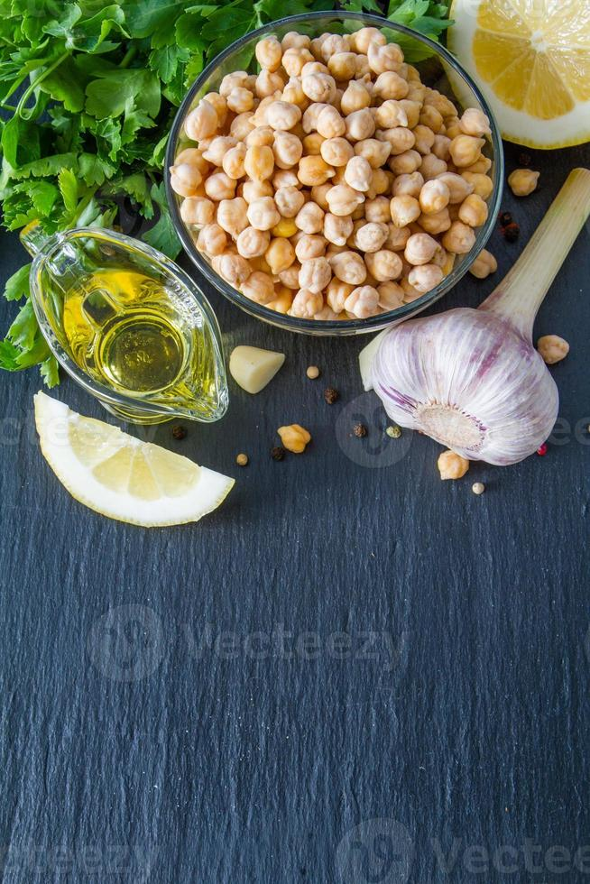 Hummus-Zutaten - Kichererbse, Zitrone, Knoblauch, Sesam, Öl, Pfeffer, Petersilie foto
