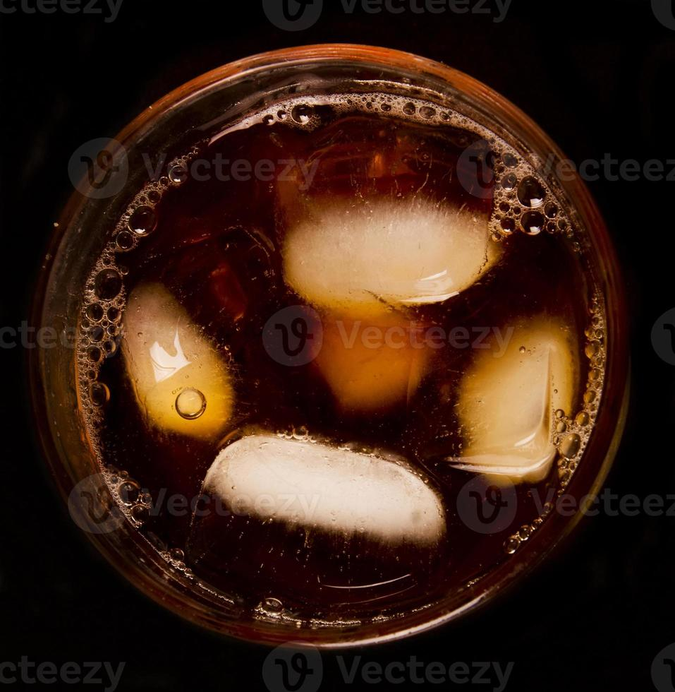 Glas mit dunkler Flüssigkeit voll mit Eis foto