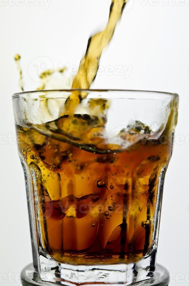 Cola wird in ein Glas gegossen foto