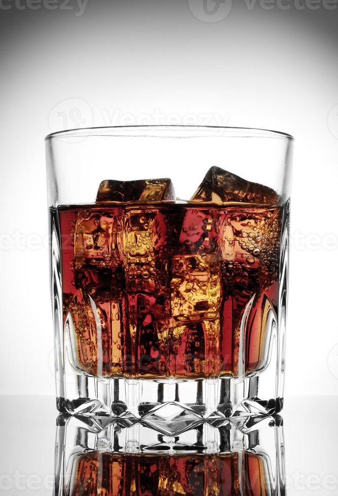 facettiertes Glas Cola mit Eis foto