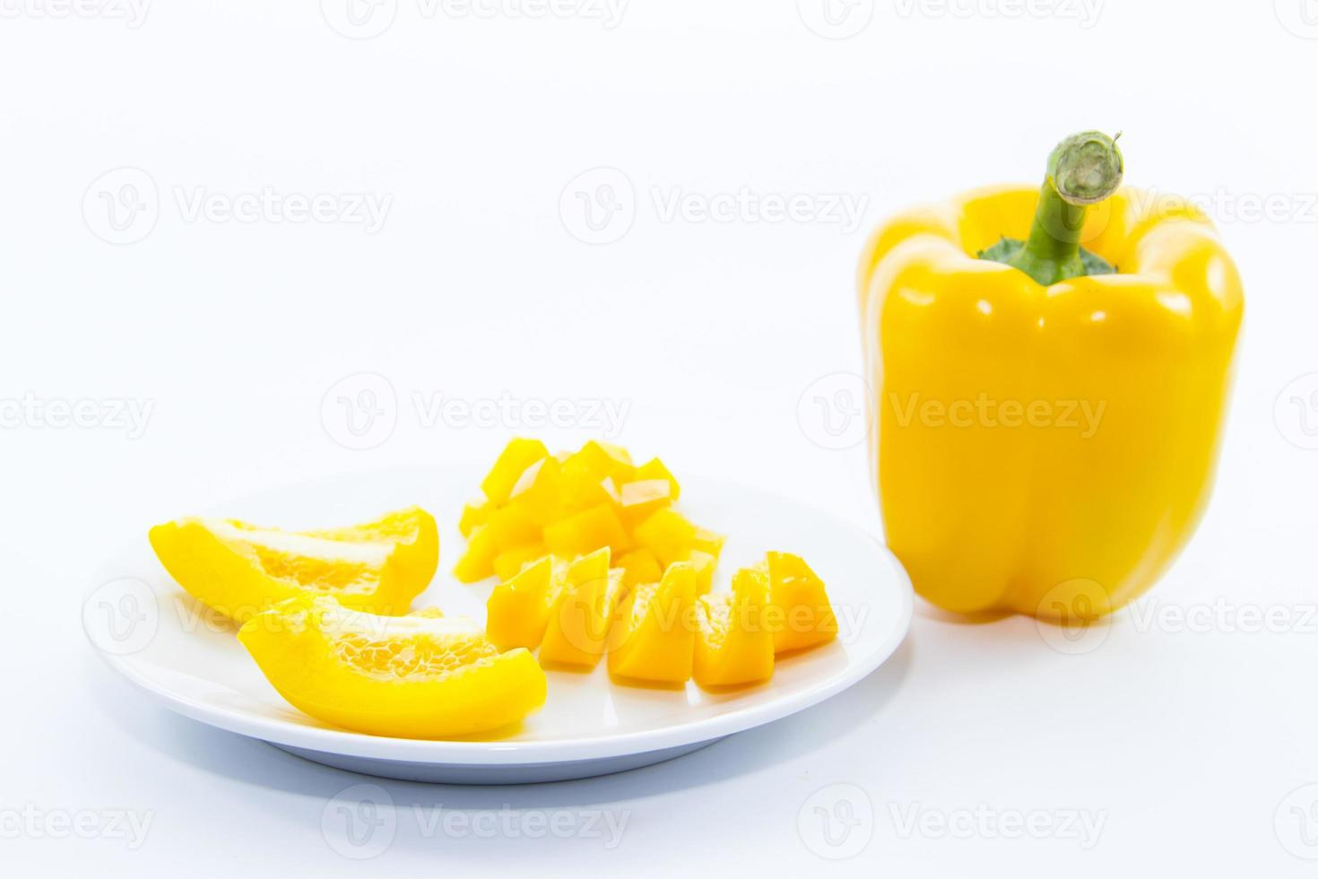 geschnittene gelbe Glocken-Chili-Zutat auf weißem Teller foto