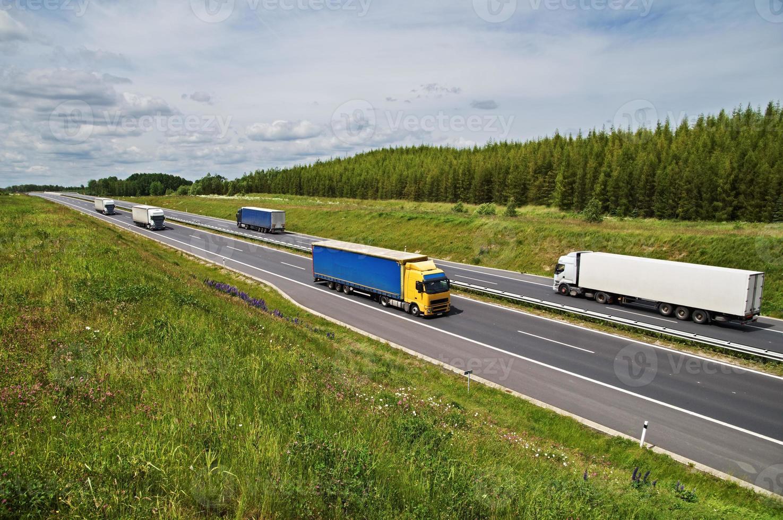 Lastwagen, die auf einer Asphaltstraße zwischen Blumenwiesen fahren foto