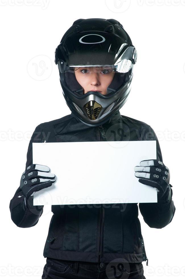 Frau in der Motorradkleidung, die eine weiße Tafel hält. foto