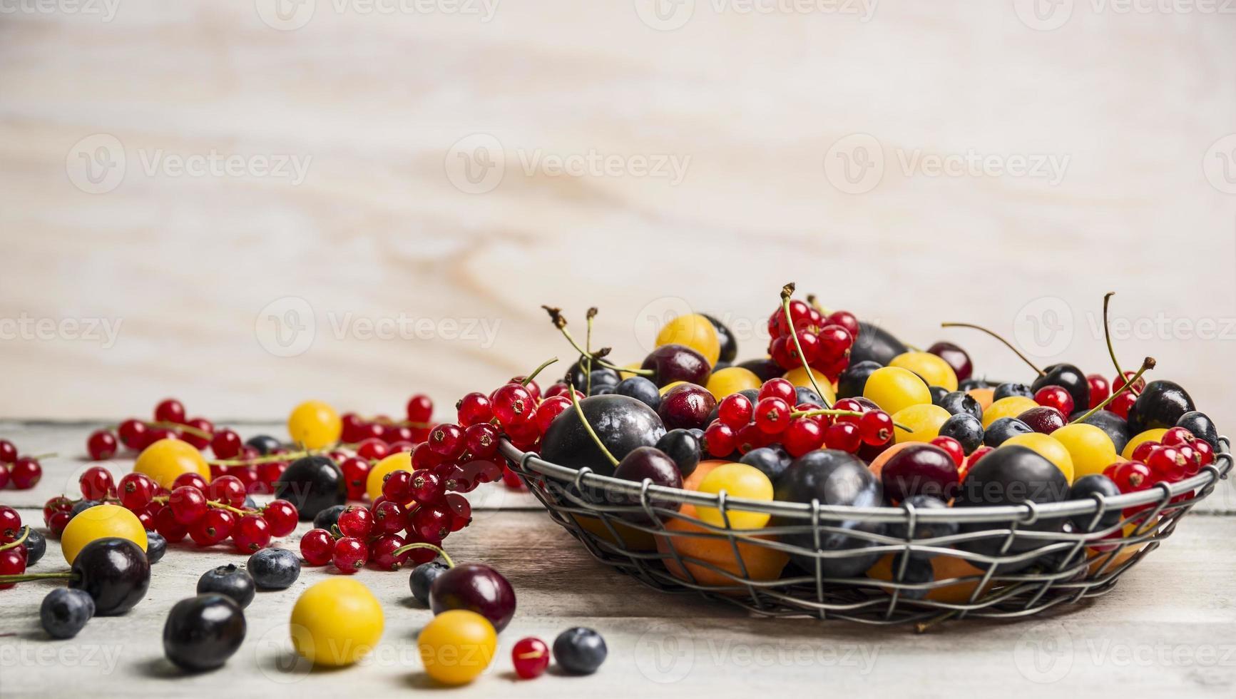 verschiedene Beeren in einem Korb auf einem weißen Hintergrund foto