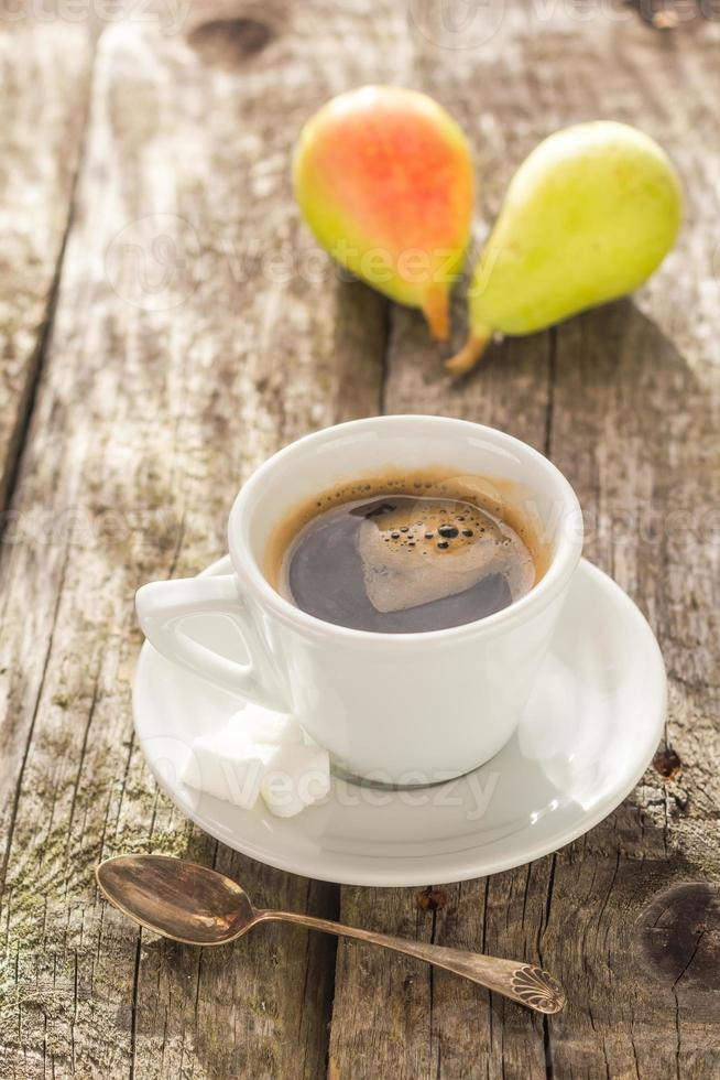 Kaffeetasse schwarz Holzbrett braune Birnen weiß foto