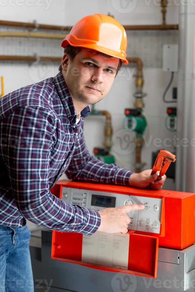 Ingenieur, der die Heizungsarbeiten am Armaturenbrett der automatisierten Steuerung anpasst foto
