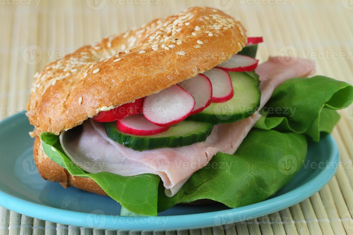 Bagel mit Schinken, Salat, Gurke und Radieschen, Nahaufnahme foto