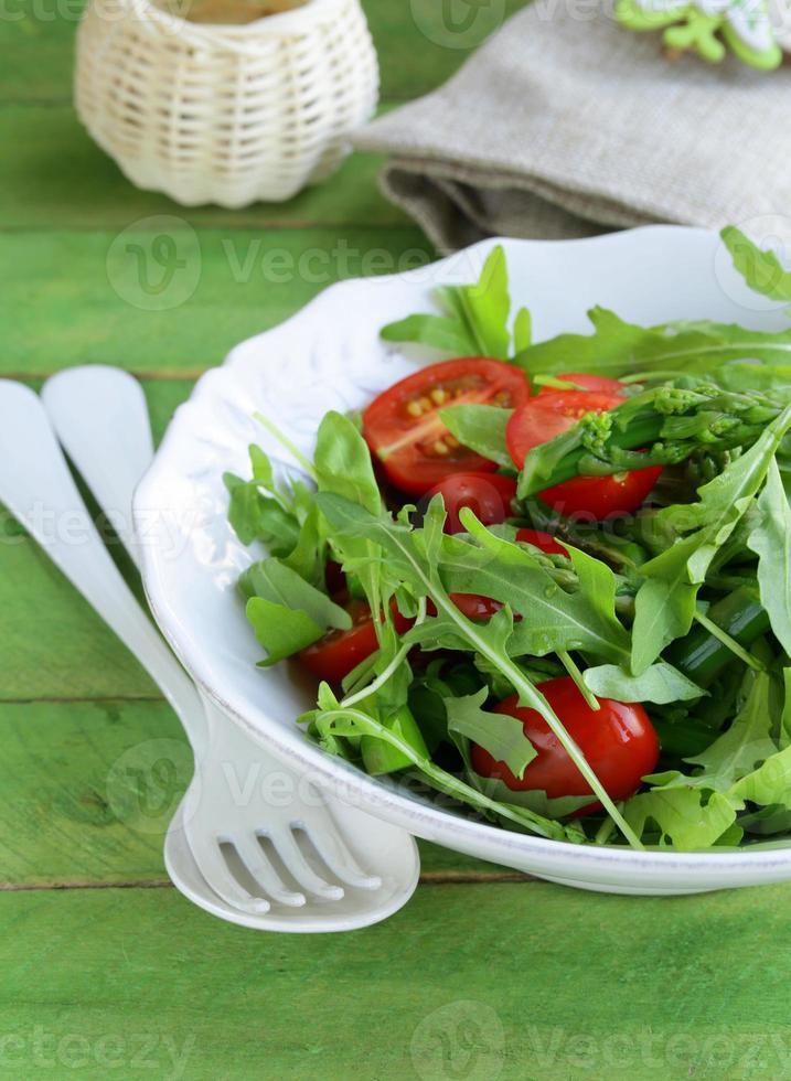 Salat mit Rucola und Tomaten auf einem Holztisch serviert foto