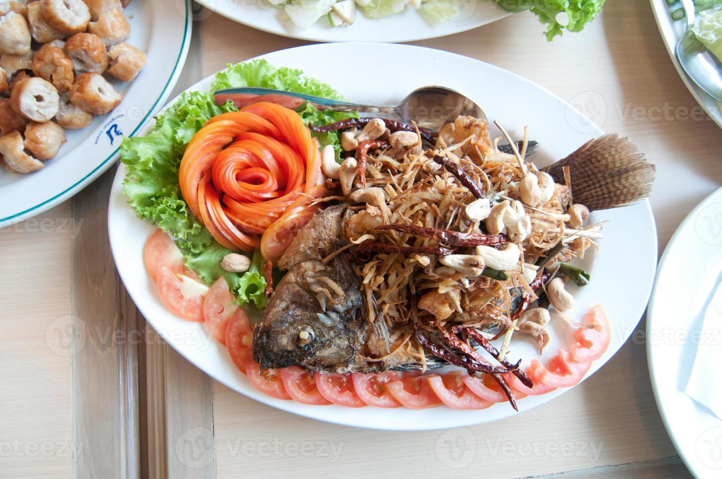gebratener Fisch mit thailändischem Essen und Kräuterbeilage foto