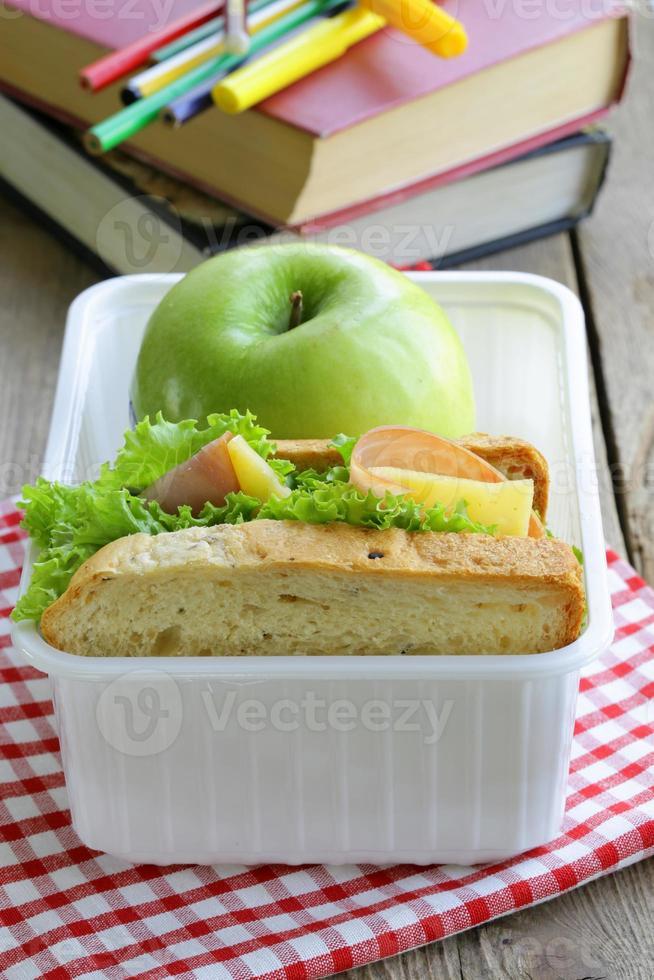 Sandwich mit Schinken, grünem Salat und Apfel in einer Box foto