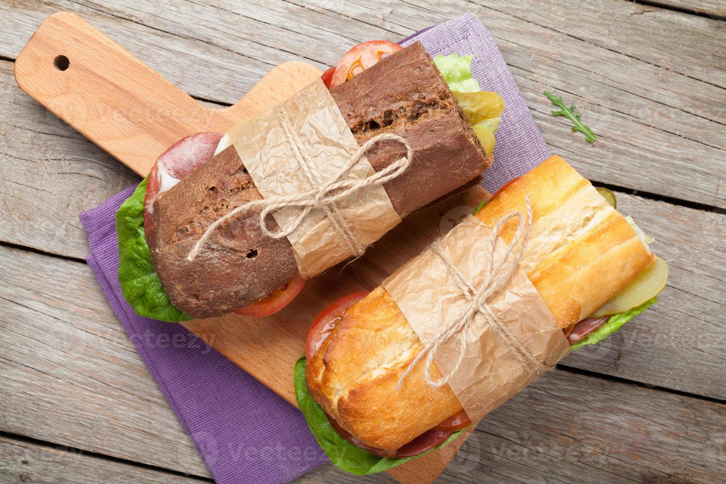 zwei Sandwiches mit Salat, Schinken, Käse und Tomaten foto