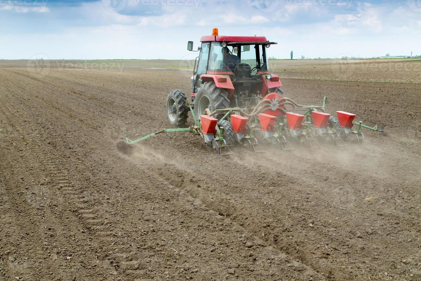 Landwirt, der Pflanzen mit pneumatischer Sämaschine sät foto