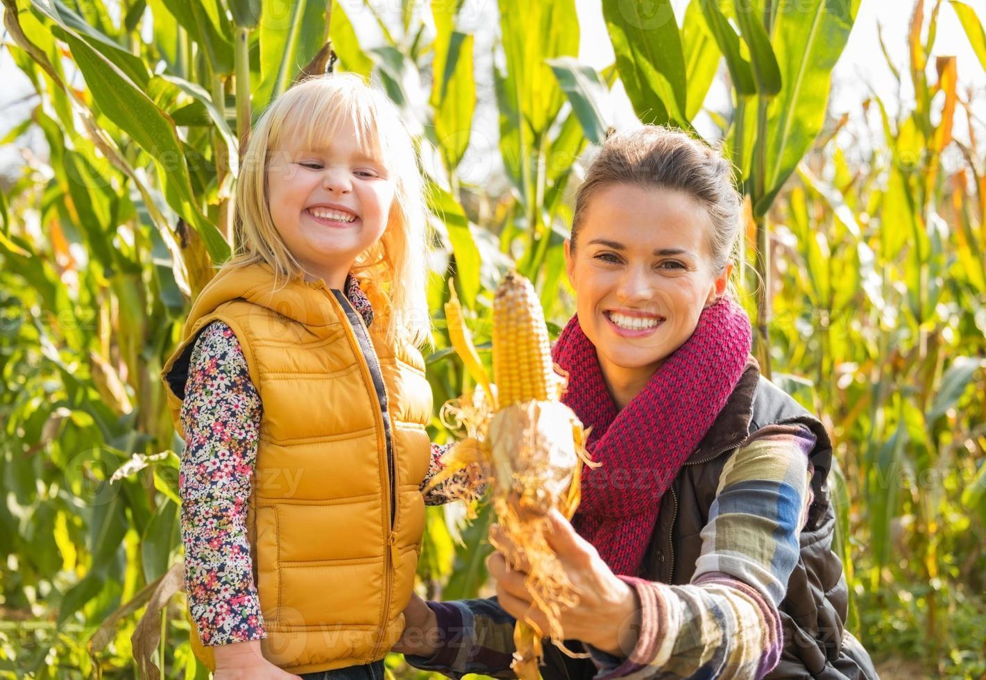 glückliche Mutter und Kind, die Mais zeigen, während in Maisfeld foto